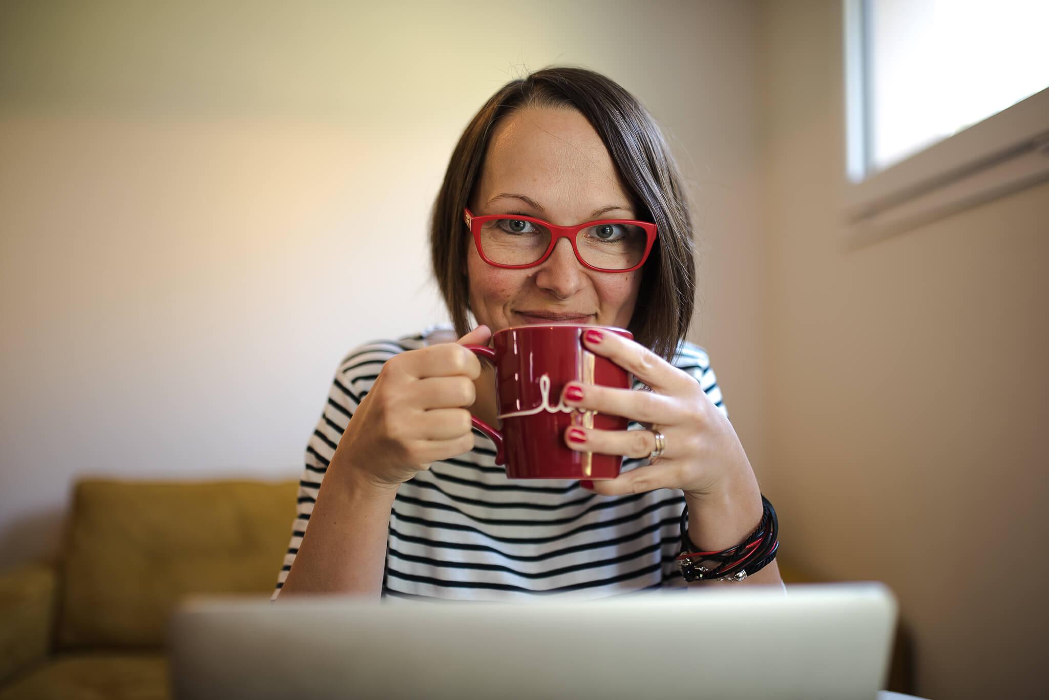 Iza z kubkiem patrząca znad komputera